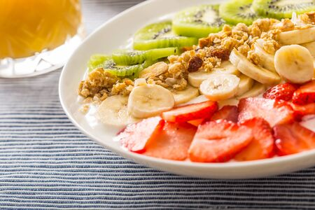 Healthy breakfast served with plate of yogurt muesli kiwi strawberries and banana. 스톡 콘텐츠