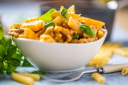 Pasta penne with chicken pieces mushrooms basil and parmesan cheese  Italian food in white bowl on kitchen table. Reklamní fotografie
