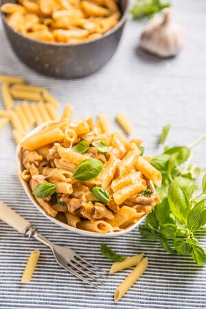 Pasta penne with chicken pieces mushrooms basil and parmesan cheese  Italian food in white bowl on kitchen table. Imagens