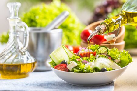 Olive oil pouring in to the fresh vegetable salad. Healthy mediterranean italian or greek cuisine.