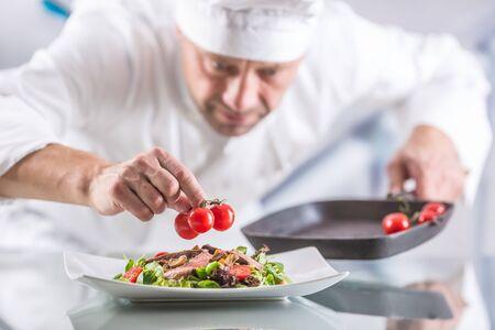 Chef-kok in de keuken van het hotel of restaurant versiert het eten vlak voor het opdienen.