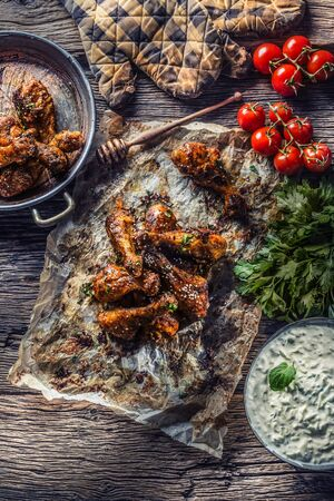 Roasted chicken legs barbecue on baked paper with tzatziki sauce tomatoes and parsley herbs - Top of view. Reklamní fotografie