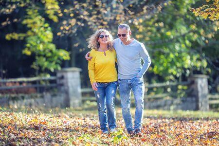 가을 공원에서 행복한 성숙한 부부는 포옹을 하고 낙엽 위를 걸어갑니다. 스톡 콘텐츠