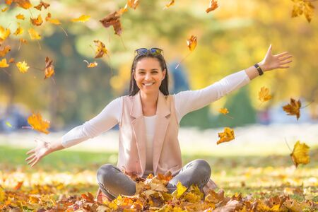 Happiness woman sitting in autumn park holding bouquet with fall leaves.