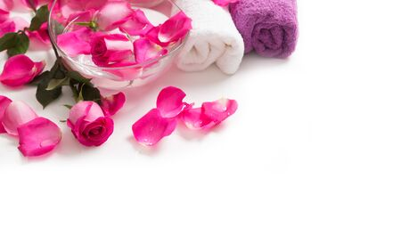 Pink roses petals in bowl with towels and pure water over white.. Spa and wellness concept.