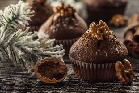 Christmas chocolate delicious muffins sprinklad with sugar powder and wallnut on top. Reklamní fotografie
