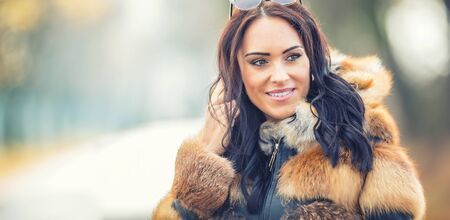 Autumn portrait of attractive young woman in warm clothing from polar fox.