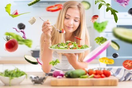 Young happy blonde girl eating healthy salad from arugula spinach tomatoes olives onion and olive oil. Healthy vegetable concept. Imagens