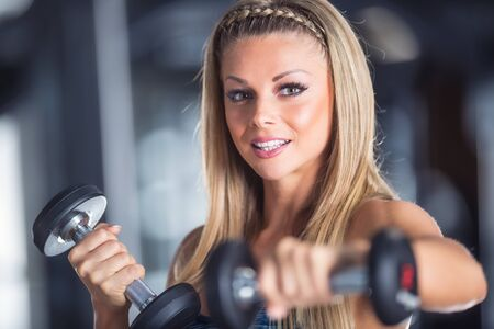 Sporty beautiful young woman practicing with dumbbells in gym.