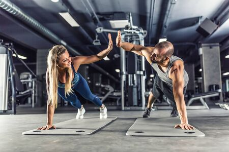 Sport couple doing plank exercise workout in fitness centrum. Man and woman practicing plank in the gym. Stock Photo