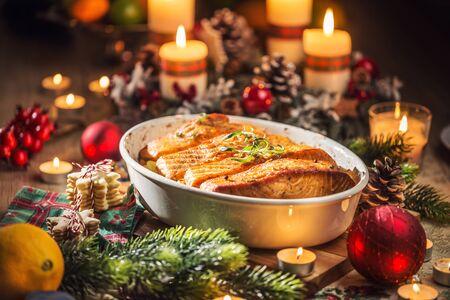 Weihnachtsessen aus Fischlachs im Bräter mit festlicher Dekoration Adventskranz und brennenden Kerzen.