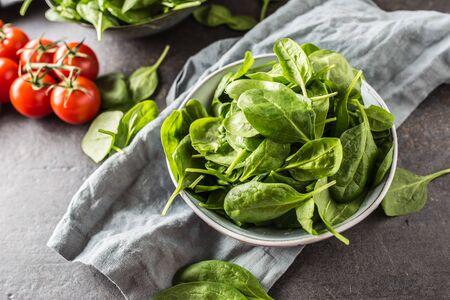 Fresh baby spinach in bowl on dark kitchen table. Reklamní fotografie