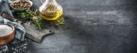 Organic food concept with olive oil salt peppet rosemary and kitchen utensil - butcher knife. Reklamní fotografie