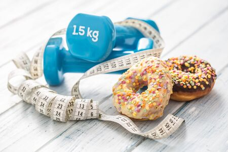 Sweet glazed donuts with dumbbells and measure tape on table.