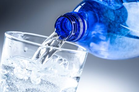 Pouring mineral water from blue bottle into clear glass on abstract grey background.