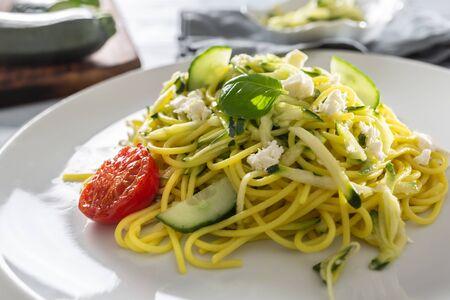 Spaghetti zucchini raw vegan pasta with feta cheese cucumber and basil. Imagens