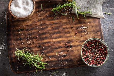Top view shot of square wooden cutting board and rustic cleaver on dark metalic background with spices, fresh rosemary and salt seasoning after meat was taken away. Food preparation items.
