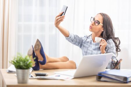 Lazy secretary with her feet up taking a selfie with a coffee in her hand.