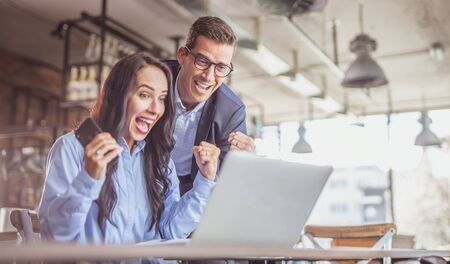 Businesswoman and businessman colleagues celebrate a success with enthusiastic facial expressions looking at the notebook screen.