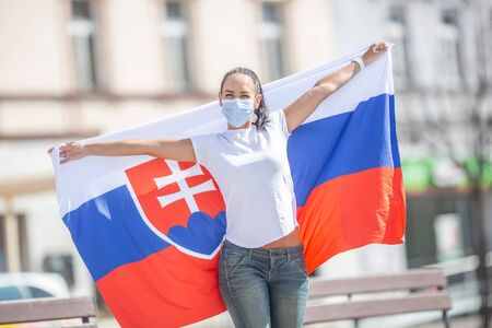 Smiling girl in a face mask holds a flag of Slovakia behind her on the street. Reklamní fotografie