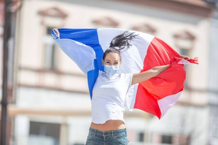 Female in a face mask holds a French flag on the street, celebrating a victory.