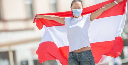 Young female in face mask holds Austrian flag on the street.