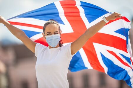 Woman in face mask holds a UK flag during the stay strong campaign.