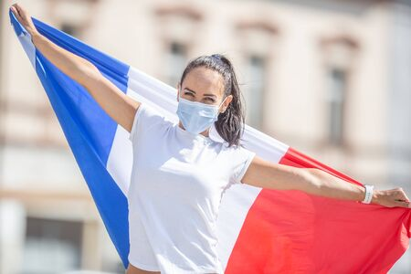 Female in a face mask holds a French flag on the street.