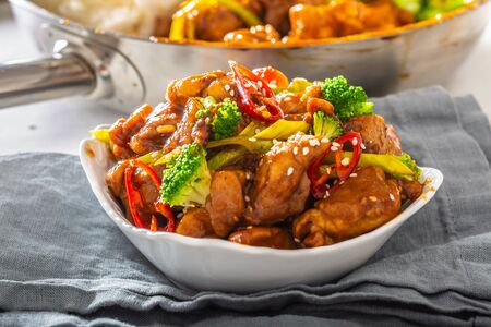 Bowl of teriyaki chicken sprinkled with seesame seeds, fresh chillies and broccoli.