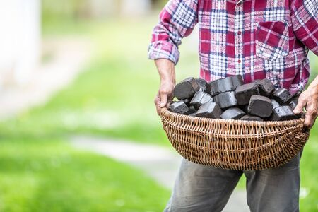 Man carrying basket full of coal briquettes in the backyard of his house. Stock Photo