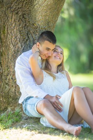 Young lovers sitting under the tree, girl stroking the boy's neck, smiling on a hot sunny summer day.