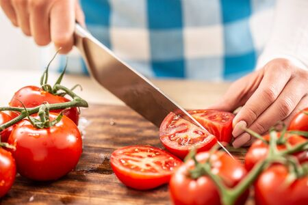 Detail of female hands cutting a tomato by a knife on a chopping board with more fresh tomatoes around.