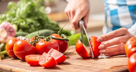 Detail of a tomato freshly cut into halves on a cutting board with cucumber, garlic and more tomatoes aside. Stok Fotoğraf