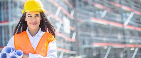 Female architect wearing orange safety vest and a yellow helmet holds rolled construction plans under her armpit in front of the unfinished building.