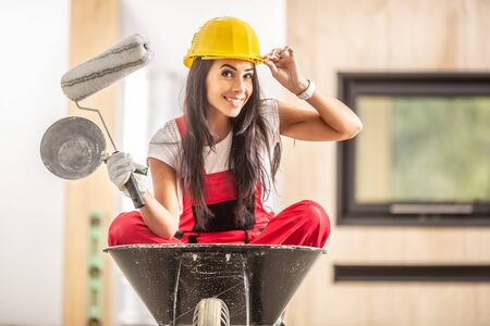Beautiful girl sitting in a wheelbarrow inside the construction site with building tools in her hands wearing overall and a hard hat.
