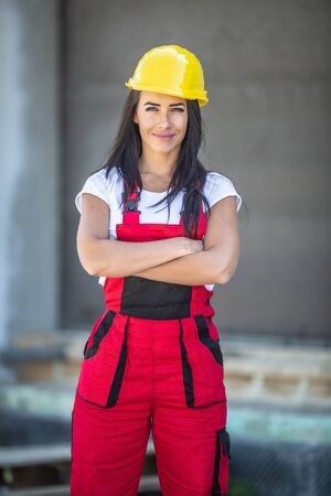 Female builder stands with arms crossed on a construction site dressed in work overalls and a yellow hard hat.