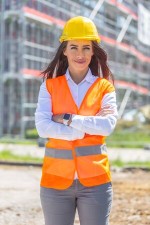 Female businesswoman wearing jeans, safety vest and helmet stands confidently in front of the construction covered in scaffolding. Banco de Imagens