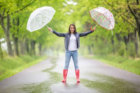 Gorgeous woman stands on a rainy asphalt road in the nature holding two umbrellas with arms wide open.