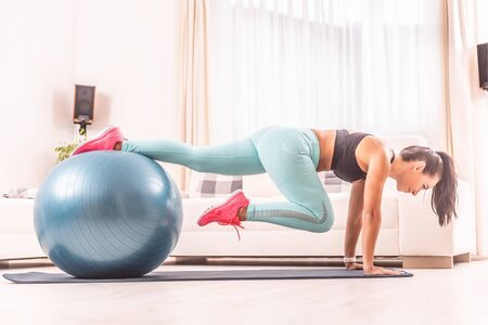 Athletic woman in her 30s working out at home using fit ball and a mat.