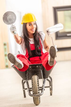 Beautiful girl sitting in a wheelbarrow inside the construction site with building tools in her hands wearing overall and a safety helmet.