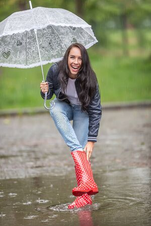 Woman laughing at water leaking to her rain boot, taking it off, while she keeps protecting herself againt the rain by an umbrella.