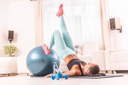 Female working out at home, lifting her core from the ground, one leg stretched, one leg on a fit ball. 版權商用圖片