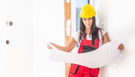 Female construction supervisor studies building plans in the red overall and yellow safety helmet. Banco de Imagens