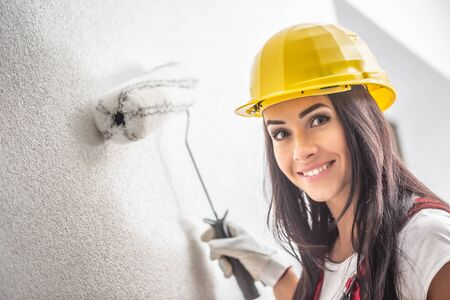 Smiling pretty female with a helmet painting the wall with a roller. Banco de Imagens