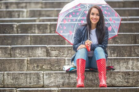 Pretty girl awaits her date sitting on stone stairs protecting herself from rain by an umbrella.