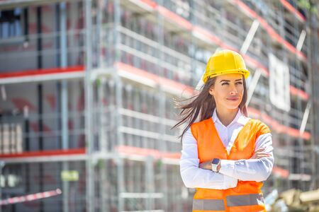 Female site supervisor wearing safety vest and helmet stands confidently in front of the construction covered in scaffolding.