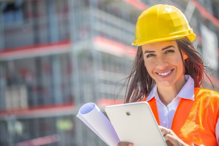 Smiling woman in PPE holds a tablet and a blueprint with a construction site in the background. Banco de Imagens