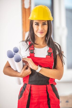 Good looking female construction planner holding blueprints dressed in working clothes and helmet inside the house. Banco de Imagens