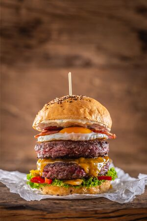 Double beef burger with cheese, fried egg, bacon, salad and peppers.