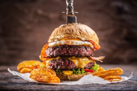 A knife-stabbed double-beef burger with melted cheese, fried egg and bacon, salad and paprika potato wedges.